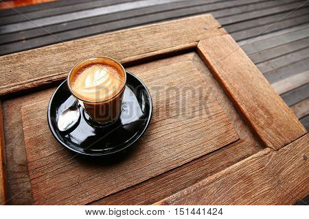 piccolo latte hot coffee drinking on wooden table