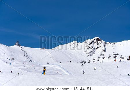 Skiers, chairlift and easy giant slalom course in Alpine ski resort in Solden in Otztal Alps, Tirol, Austria