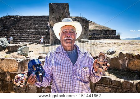 MONTE ALBAN, MEXICO -DEC 8, 2015: Unknown old man selling mayan  mask, on Dec 8, 2015, at Monte Alban ancient Zapotec capital, near Oaxaca, Mexico.