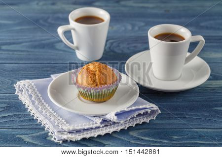 Fresh muffins on the blue wooden table