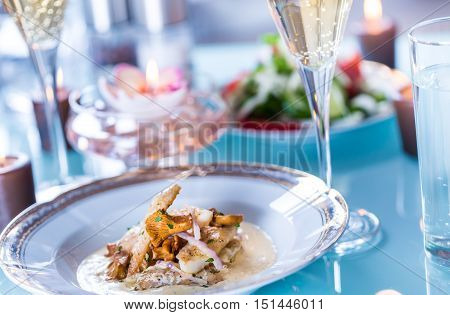 Close-up of Table with Food, Plates, Candles and Champagne Flutes