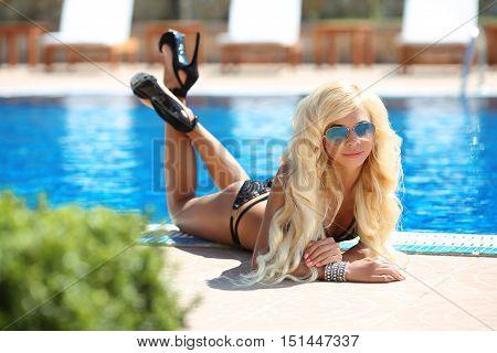 Beautiful Sexy Woman Bikini Model In Fashion Sunglasses Tanned And Lying By The Blue Swimming Pool,