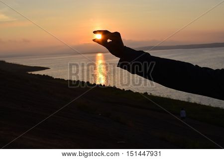 silhouette hand capture the sun in sunset