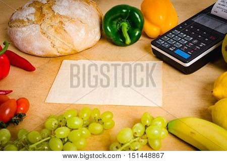 cash register and blank paper on the table with vegetables