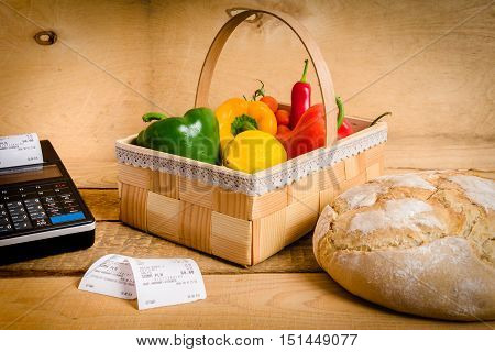basket of vegetables on a wooden table with a cash register