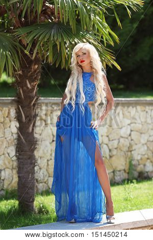 Attractive Fashion Blond Woman Model Posing In Blue Long Dress On Party, Outdoor Portrait.