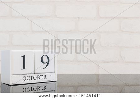 Closeup white wooden calendar with black 19 october word on black glass table and white brick wall textured background with copy space view another more date in my portfolio