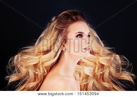 Beautiful Woman with Windy Hair. Blonde Curly Hairstyle and Makeup