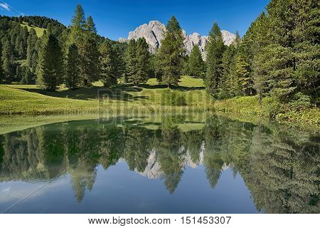 Lake In The Forest With The Mountains In Background, Dolomites