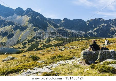 Girl Sitting On A Rock And Admires The Mountain.