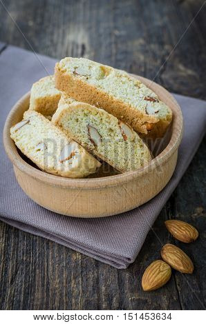 Italian cantuccini cookies in a bowl with almonds. Traditional italian almond cookies biscotti on old wooden background. Homemade cookies on wooden table. Delicious cookies biscotti. Selective focus.