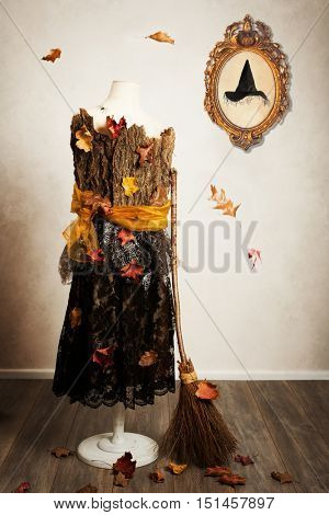 Mannequin dressed for the fall with witches broom and hat in picture frame on the wall