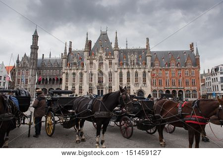 horse carriages before city hall in Brugge