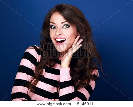Surprised Woman With Opened Mouth And Big Eyes Holding Hand The Face And Looking Happy On Blue Backg