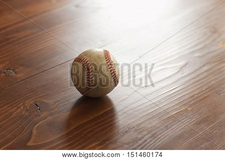 A selective focus view of an old baseball on a pine wood background