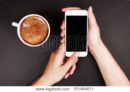 Woman using a touch screen of smart phone on the black satine table, in cafe, with cup of aromatic cappucino. Top View, flat lay style.