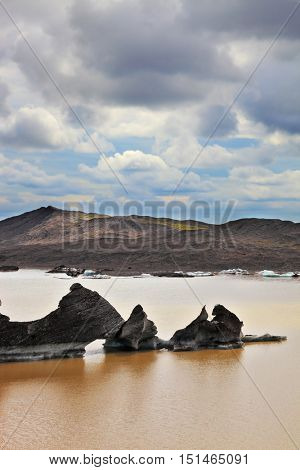 Skaftafell National Park. Ice covered with volcanic ash. Mirror Lake, formed as a result of thawing of a glacier Vatnajokull glacier spurs. Iceland in summer