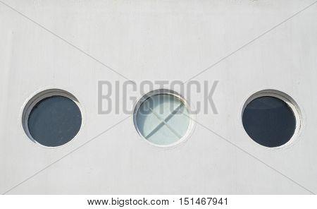 Three porthole of white sailing ship closeup