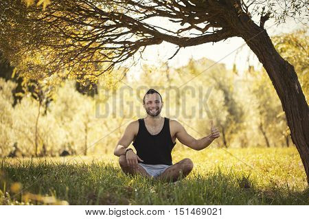 Yoga Outdoors In Warm Autumn Park. Sinlight Effect. Man Sits In