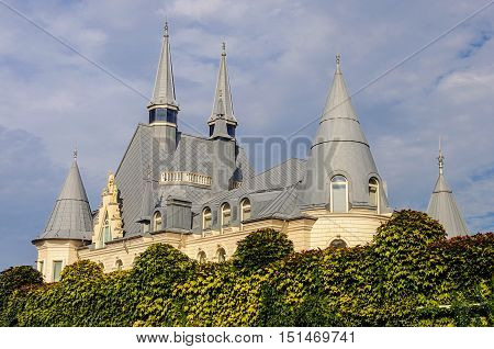 Odessa Ukraine - August 30 2016: New white castle behind a high fence overgrown with hops
