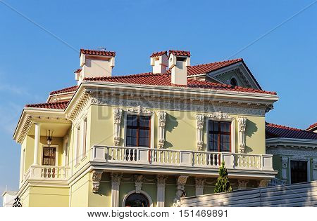 Top of beautiful two-storied yellow cottage with balcony baroque style. Odessa Ukraine