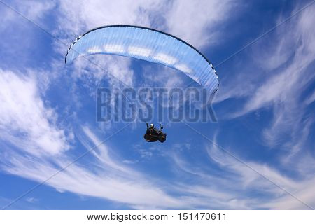 Paragliding on background of blue summer sky and white clouds