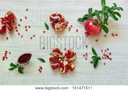 A pomegranate on a branch with leaves, the broken pomegranates, seeds, leaves, gravy boat on a light wooden background. Pomegranate fruits and seeds. Horizontal. Top view.