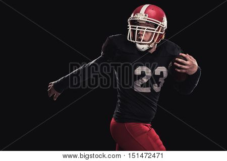Soccer player on a dark background in vintage style. The classic American game. college Students. dynamic movement. the player runs away from the enemy