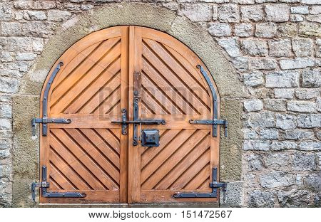 Double wooden door and stone wall - Ancient wooden door with metal hinged and latch on a weathered stone wall