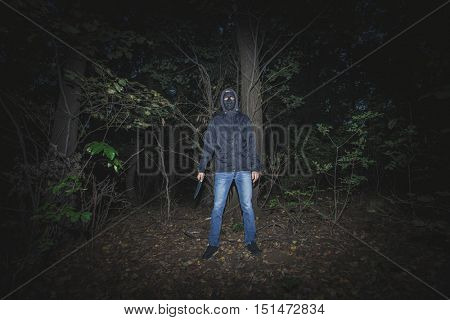 man with mask and knife in the wood Halloween night