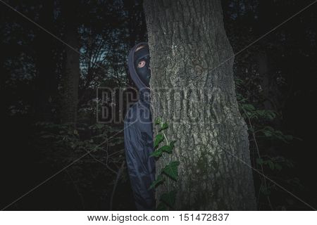 man with black mask in the wood Halloween night