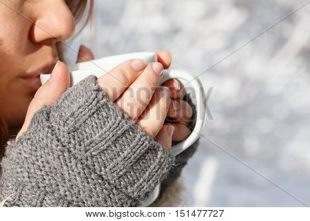 Beautiful young woman in gray fingerless knitted mittens drinking from white cup at the background of snowy forest. Close up.