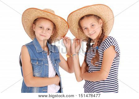 Two pretty twelve year old girls wearing a big floppy straw sun hat isolated on white