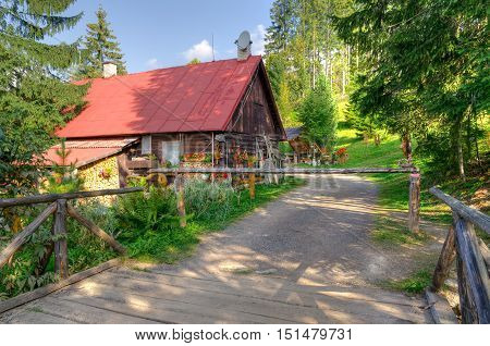 Summer rural landscape. Wooden hut on a mountain trail.