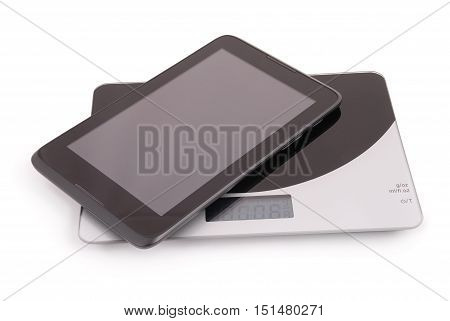 Black tablet pc isolated lies on the scales on a white background. Clipping path inside.