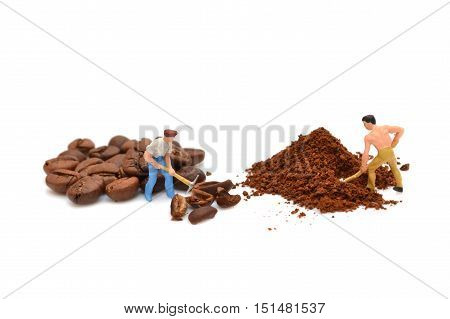 Miniature people grind coffee. Little people break coffee beans. Ground coffee. Macro. Figures of people. Statuette. Handful of coffee