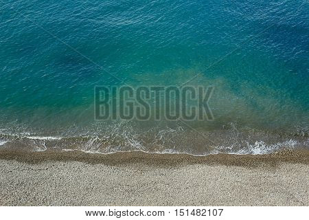 Beach stuff placed near sea. Beautiful beach and tropical turquoise blue sea from above