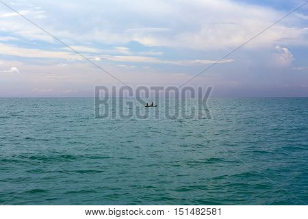 Two people in the sea in a rubber boat. Beautiful tropical turquoise blue sea from above