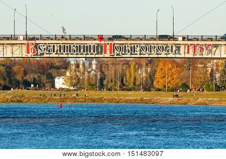 VELIKY NOVGOROD RUSSIA - OCTOBER 9 2016. Road bridge across the Volkhov river in Veliky Novgorod Russia with the inscription Veliky Novgorod 1157 - autumn city landscape at the sunset