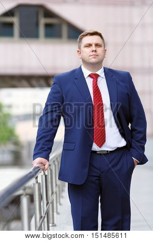 portrait of handsome young businessman in blue suit walking outdoors