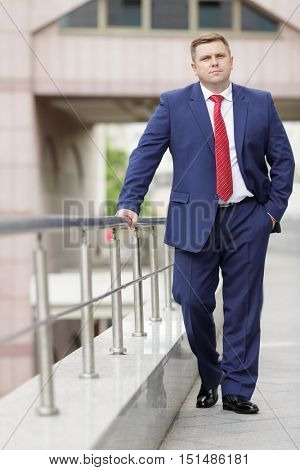 Portrait of handsome young businessman in suit walking outdoors