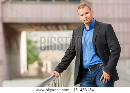 half growth portrait of handsome young businessman in black jacket, jeans and blue shirt walking outdoors