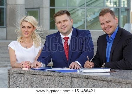 outdoors image of friendly business team (two man and woman) communicating outside