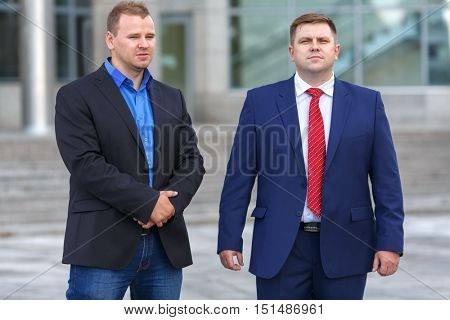 Two successful mature businessman well-dressed standing together outside