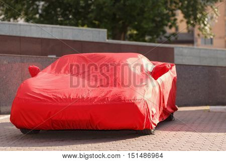 luxurious red roadster in cover protects against rain of dust and dirt