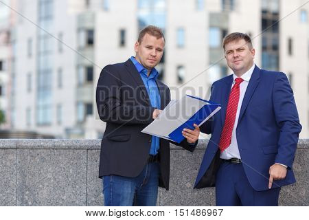 Two successful mature businessman well-dressed standing together outside in hands of single envelope