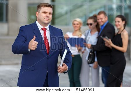 well dressed business team leader and four co-workers in background, gesturing thumbs up