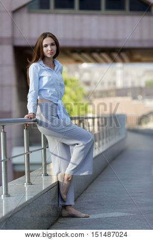 pretty young girl in light dress posing on street leans on railing