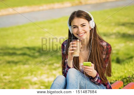 Closeup of beautiful millennial teenage girl in park in spring, with headphones, smart phone and takeaway coffee, smiling, looking at camera. Natural light, mild retouch.