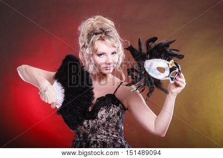 Holidays people and celebration concept. Woman blonde middle aged model holding in hand black carnival mask feather fan on festive color background